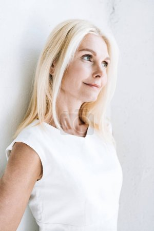Photo for Smiling blonde mature woman looking away near white wall - Royalty Free Image