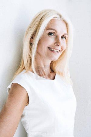 happy blonde mature woman near white wall