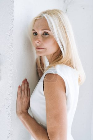 Photo for Dreamy blonde mature woman near white wall - Royalty Free Image