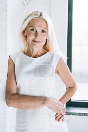 Photo for Smiling blonde mature woman near white wall and window - Royalty Free Image