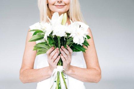 Photo pour Vue recadrée de femme mûre blonde heureuse avec des fleurs blanches d'isolement sur le gris - image libre de droit