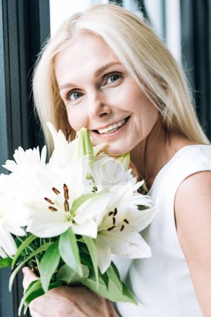 Photo for Portrait of happy blonde mature woman with white flowers near window - Royalty Free Image