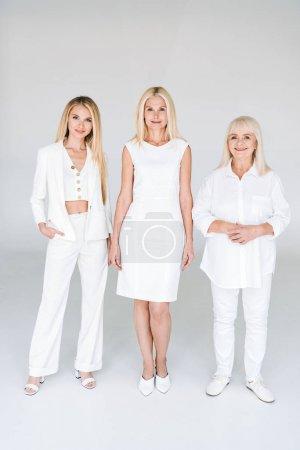 Foto de Vista de longitud completa de tres generaciones mujeres rubias en gris - Imagen libre de derechos