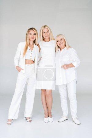 Photo pour Vue complète de trois générations de femmes blondes étreignant sur le gris - image libre de droit