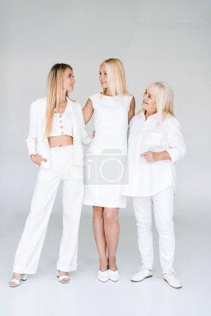 Photo pour Vue complète de trois générations de femmes blondes se regardant sur le gris - image libre de droit