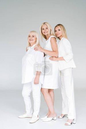 Photo pour Vue pleine longueur de trois femmes blondes de génération posant sur le gris - image libre de droit