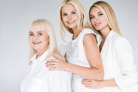 Photo for Side view of three generation blonde women isolated on grey - Royalty Free Image