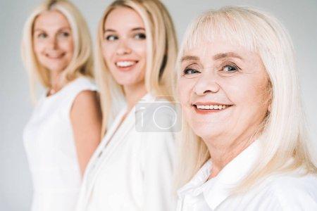 Photo pour Focus sélectif de trois femmes blondes génération isolées sur le gris - image libre de droit