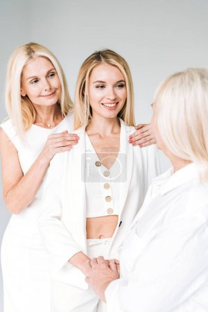 Photo for Three generation blonde smiling women isolated on grey - Royalty Free Image
