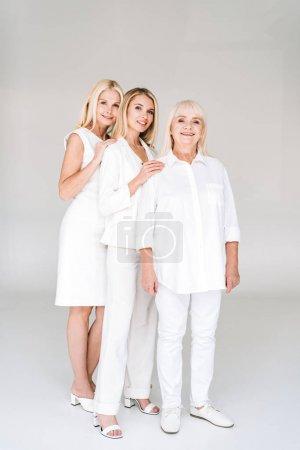 Foto de Vista de longitud completa de tres generaciones sonriendo mujeres rubias en gris - Imagen libre de derechos