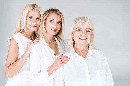 Foto de Tres generaciones sonriendo mujeres rubias aisladas en gris - Imagen libre de derechos