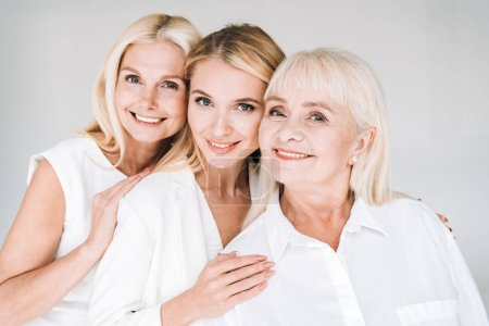 Photo for Cheerful three generation blonde women isolated on grey - Royalty Free Image