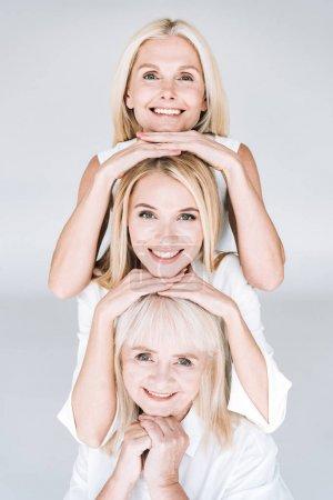 Foto de Hermosa sonriendo tres generaciones mujeres rubias aisladas en gris - Imagen libre de derechos