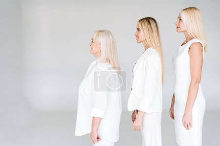Photo for Side view of smiling three generation blonde women isolated on grey - Royalty Free Image