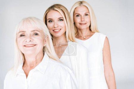 Foto de Enfoque selectivo de atractivas mujeres rubias de tres generaciones aisladas en gris - Imagen libre de derechos
