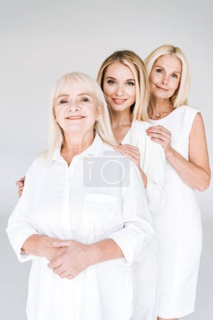 Foto de Tres generaciones de mujeres rubias de pie aisladas en gris - Imagen libre de derechos