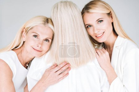 mother and daughter hugging senior woman isolated on grey
