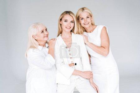 Foto de Tres generaciones mujeres rubias sonriendo aisladas en gris - Imagen libre de derechos