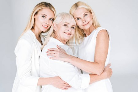 Photo for Three generation blonde women embracing isolated on grey - Royalty Free Image