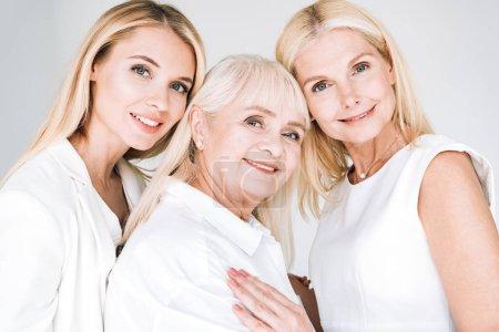 Foto de Tres generaciones mujeres rubias abrazando aisladas en gris - Imagen libre de derechos