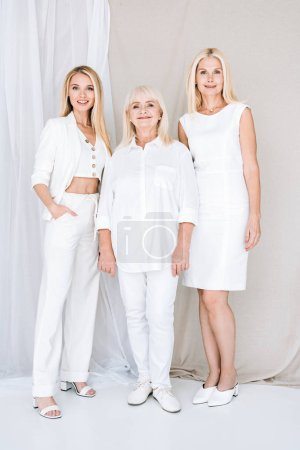 Photo pour Vue pleine longueur de trois femmes blondes génération dans des tenues blanches totales - image libre de droit
