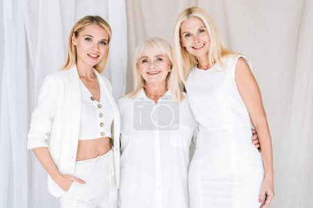 Foto de Elegante mujeres rubias de tres generaciones en trajes blancos totales - Imagen libre de derechos