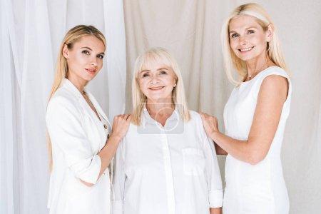Foto de Sonriendo elegante mujeres rubias de tres generaciones en trajes blancos totales - Imagen libre de derechos