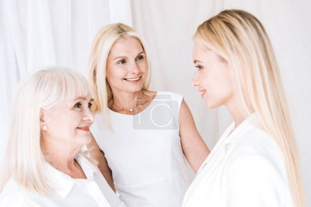 Photo for Elegant three-generation blonde women in total white outfits looking at each other - Royalty Free Image