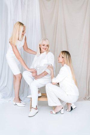 Photo pour Vue pleine longueur de la mère blonde élégante et la fille en tenue blanche totale près de la femme âgée sur la chaise - image libre de droit
