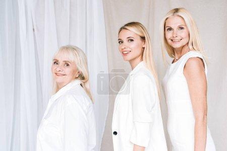 Photo pour Vue latérale de sourire les femmes blondes élégantes de trois générations dans les tenues blanches totales regardant l'appareil-photo - image libre de droit
