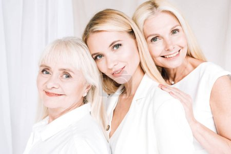 Photo pour Femmes blondes élégantes souriantes de trois générations en tenues blanches totales - image libre de droit