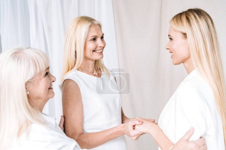 Photo for Elegant three-generation blonde family in total white outfits - Royalty Free Image