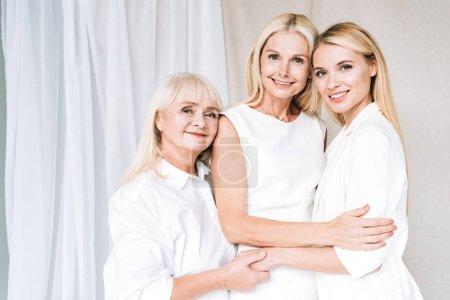 Photo pour Élégante sa blonde de trois générations femme heureuse dans des tenues blanches totales - image libre de droit