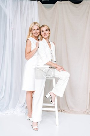 Photo pour Souriant élégant blonde mature mère embrasser doucement jeune fille sur chaise - image libre de droit