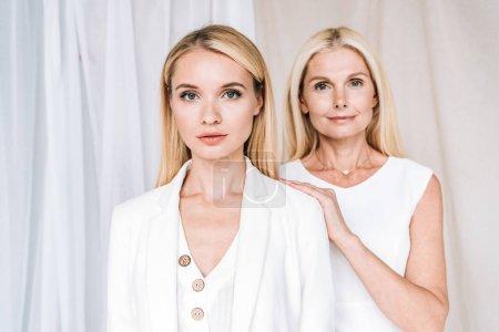 Photo pour Élégante mère blonde souriante et fille sérieuse en tenue blanche totale - image libre de droit