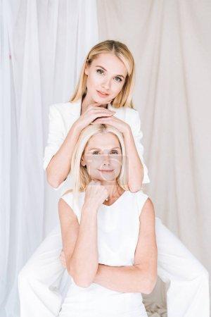 Photo pour Mère et descendant blond élégant posant dans les tenues blanches totales - image libre de droit
