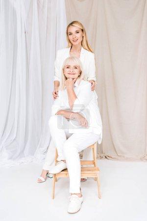 Photo pour Vue pleine longueur de la grand-mère blonde élégante et petite-fille ensemble dans des tenues blanches totales - image libre de droit