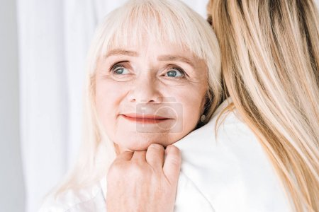 blonde smiling grandmother gently hugging granddaughter