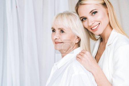 Photo pour Élégante petite-fille blonde étreignant la grand-mère souriante - image libre de droit