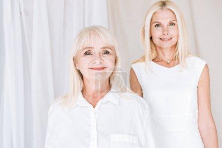 Photo pour Fille élégante de mûre blonde de sourire et mère aînée dans les tenues blanches totales - image libre de droit
