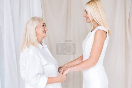 Photo for Smiling blonde mature daughter and senior mother in total white outfits holding hands - Royalty Free Image