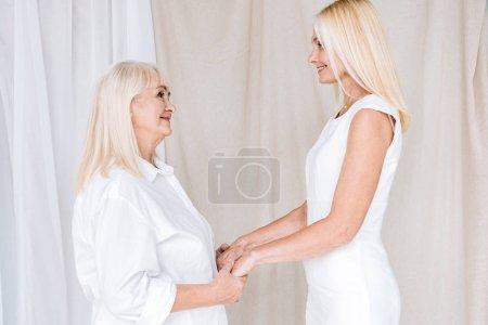Photo pour Fille mûre blonde de sourire et mère aînée dans les tenues blanches totales retenant des mains - image libre de droit