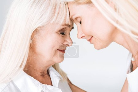 Photo for Blonde mature daughter and senior mother standing face to face with closed eyes isolated on grey - Royalty Free Image