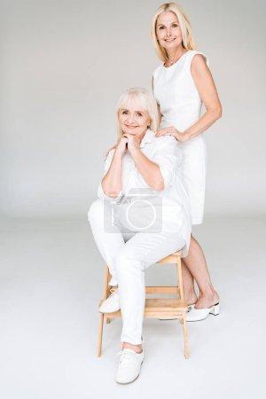 Photo pour Vue pleine longueur de la fille mûre blonde élégante et de la mère aînée dans les tenues blanches totales - image libre de droit