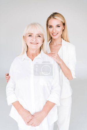 Photo for Smiling blonde grandmother and granddaughter together in total white outfits embracing isolated on grey - Royalty Free Image