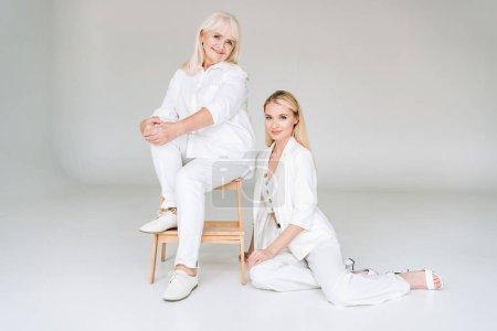 Photo pour Vue pleine longueur de grand-mère blonde souriante assise sur la chaise près de la belle petite-fille en total vêtements blancs - image libre de droit