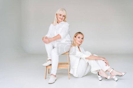 Photo pour Vue pleine longueur de grand-mère blonde souriante assise sur la chaise près de la petite-fille dans des vêtements blancs totaux - image libre de droit
