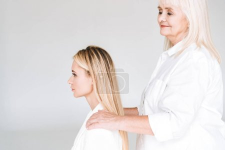 Photo for Side view of blonde grandmother putting hands on granddaughter shoulders isolated on grey - Royalty Free Image