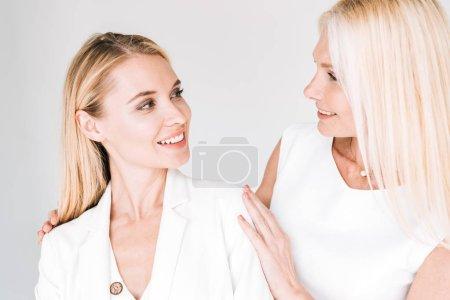 Photo pour Mère mûre blonde de sourire regardant la jeune fille dans les vêtements blancs totaux d'isolement sur le gris - image libre de droit