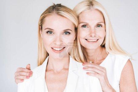 Photo pour Souriant blonde mature mère embrassant belle jeune fille en total blanc vêtements isolés sur gris - image libre de droit